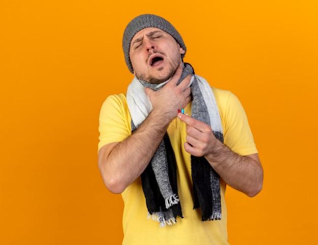 겨울 모자와 스카프를 착용하는 젊은 금발의 아픈 슬라브 남자가 목에 손을 넣고 복사 공간이 오렌지 벽에 고립 된 의료 캡슐을 보유하고 있습니다.