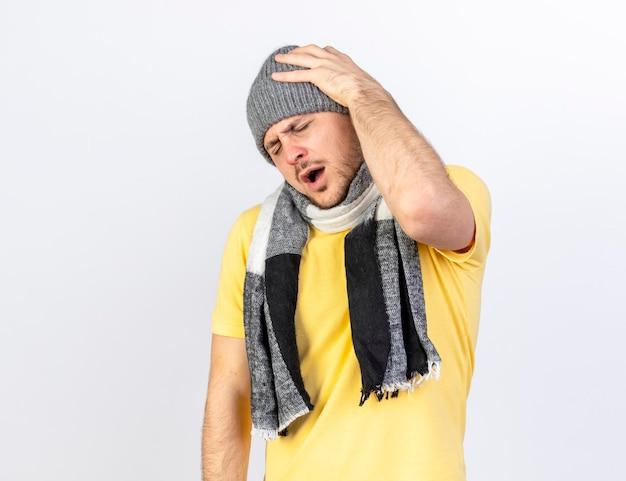 冬の帽子とスカーフを身に着けている痛む若い金髪の病気のスラブ人