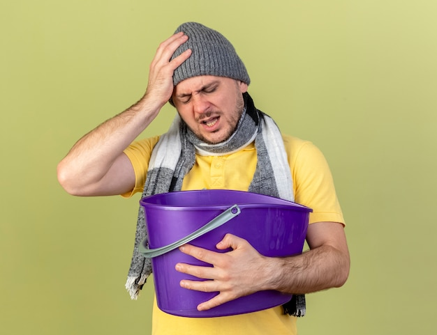 Aching young blonde ill slavic man wearing winter hat and scarf puts hand on head and holds plastic bucket isolated on olive green wall with copy space