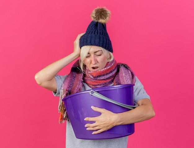겨울 모자와 스카프를 착용하는 아프고 젊은 금발의 아픈 슬라브 여자가 머리에 손을 얹고 복사 공간이 분홍색 벽에 절연 플라스틱 양동이를 보유하고 있습니다.