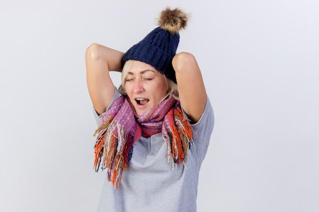 겨울 모자와 스카프를 착용하는 젊은 금발의 아픈 슬라브 여자가 복사 공간이 흰 벽에 고립 된 뒤에 머리에 손을 넣습니다.