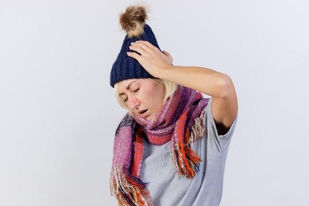La giovane donna slava malata bionda dolorante che indossa il cappello e la sciarpa di inverno mette la mano sulla testa isolata sulla parete bianca con lo spazio della copia