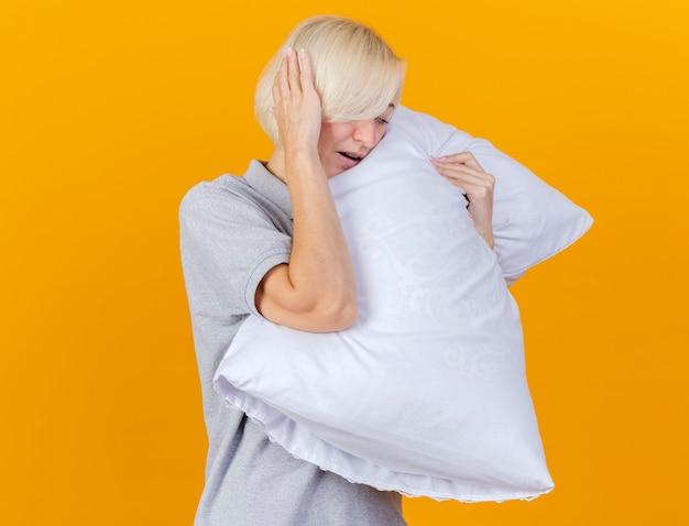 아픈 젊은 금발의 아픈 여자가 머리에 손을 넣고 오렌지 벽에 고립 된 베개를 안아