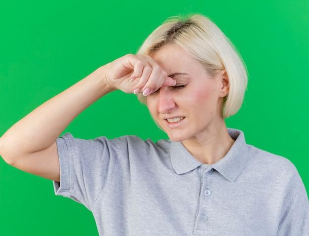Giovane donna bionda malata dolorante sta con gli occhi chiusi mettendo la mano sulla fronte isolata sulla parete verde
