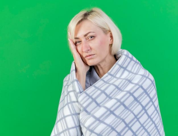 격자 무늬에 싸여 아픈 젊은 금발의 아픈 여자는 녹색 벽에 고립 된 얼굴에 손을 넣습니다