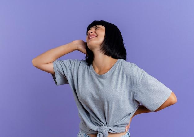 La giovane ragazza caucasica castana dolorante tiene la testa e la parte posteriore isolate su fondo viola con lo spazio della copia