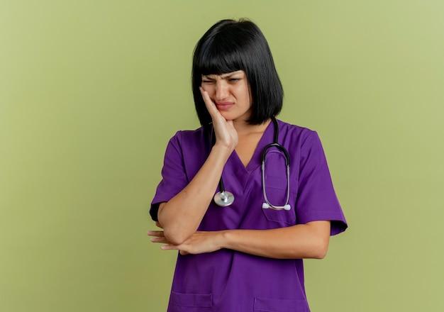 Больная молодая брюнетка женщина-врач в униформе со стетоскопом кладет руку на лицо, изолированное на оливково-зеленом фоне с копией пространства