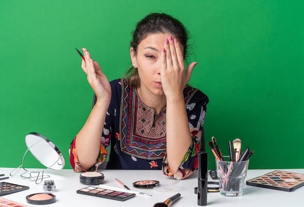 Giovane ragazza bruna dolorante seduta al tavolo con strumenti per il trucco che tiene l'eyeliner e si mette la mano sull'occhio
