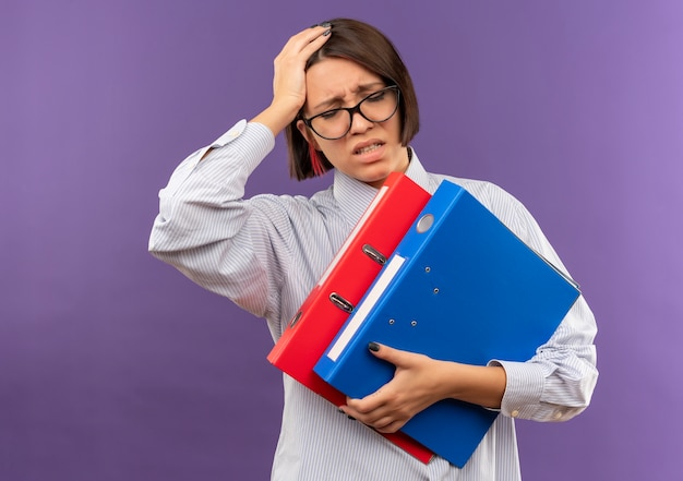 Dolorante giovane ragazza call center con gli occhiali che tengono le cartelle mettendo la mano sulla testa con gli occhi chiusi che soffrono di mal di testa isolato su viola