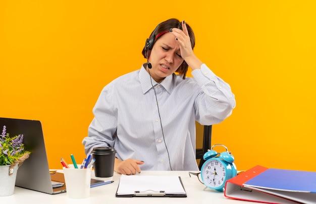 Giovane ragazza dolorante della call center che indossa la cuffia avricolare che si siede allo scrittorio che mette la mano sulla testa con gli occhi chiusi isolati sull'arancio