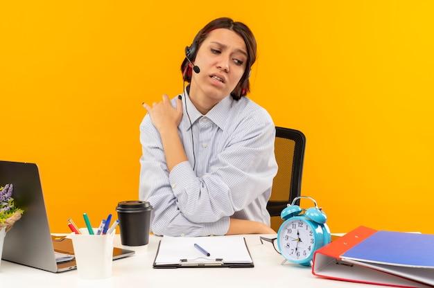 Dolorante giovane ragazza della call center che indossa la cuffia avricolare seduto alla scrivania mettendo la mano sulla spalla che soffrono di dolore isolato sull'arancio