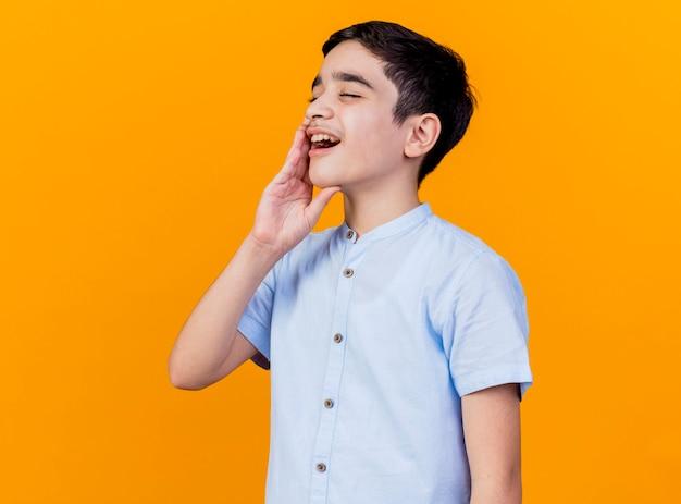 복사 공간 오렌지 배경에 고립 된 치통 데 뺨에 손을 유지 아프고 어린 백인 소년