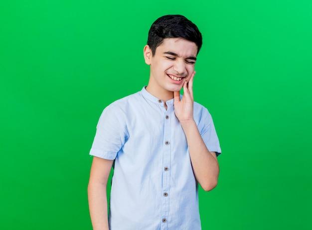 コピースペースで緑の壁に隔離された歯痛に苦しんで顔に手を維持している痛む若い白人の少年