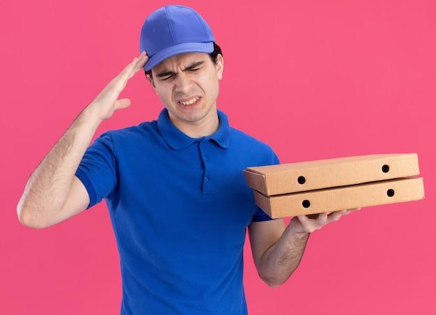 Giovane fattorino caucasico dolorante in uniforme blu e cappuccio che tiene in mano i pacchetti di pizza che toccano la testa soffrendo di mal di testa con gli occhi chiusi