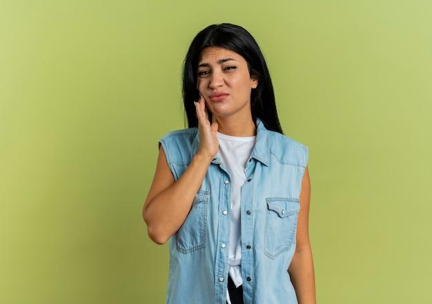 La giovane ragazza caucasica dolorante mette la mano sulla ricerca del viso