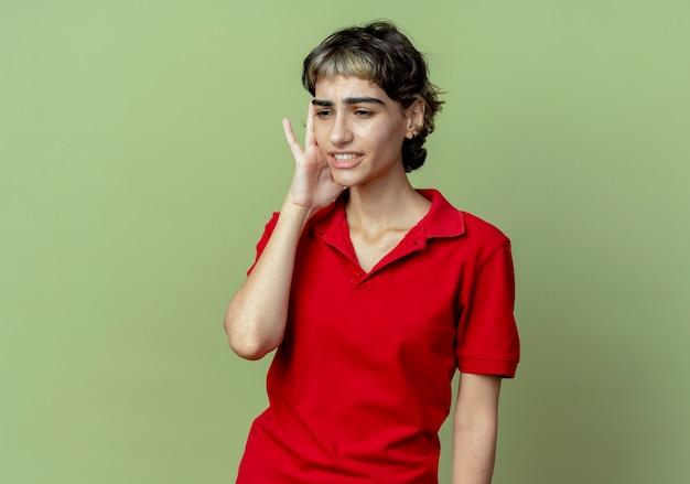 Dolorante giovane ragazza caucasica con pixie haircut mettendo la mano sul tempio guardando verso il basso che soffrono di mal di testa isolato su sfondo verde oliva con spazio di copia