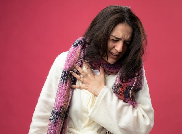 真っ赤な壁に隔離された目を閉じて胸に手を置くローブとスカーフを身に着けている痛む若い白人の病気の女の子