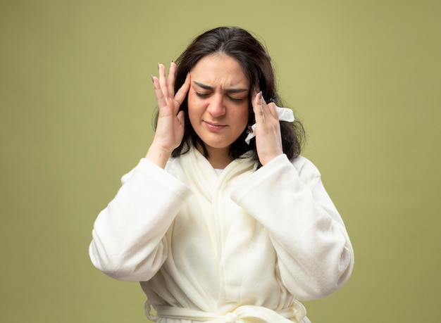 올리브 녹색 배경에 고립 된 닫힌 눈을 가진 손에 냅킨 사원에 손을 유지 가운을 입고 아픈 젊은 백인 아픈 소녀