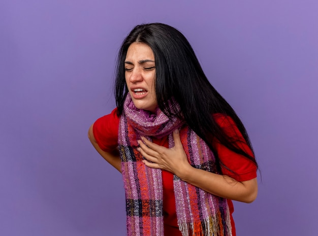 Sciarpa da portare della giovane ragazza ammalata caucasica dolorante che mette le mani sul petto e sulla schiena con gli occhi chiusi isolati sulla parete viola con lo spazio della copia