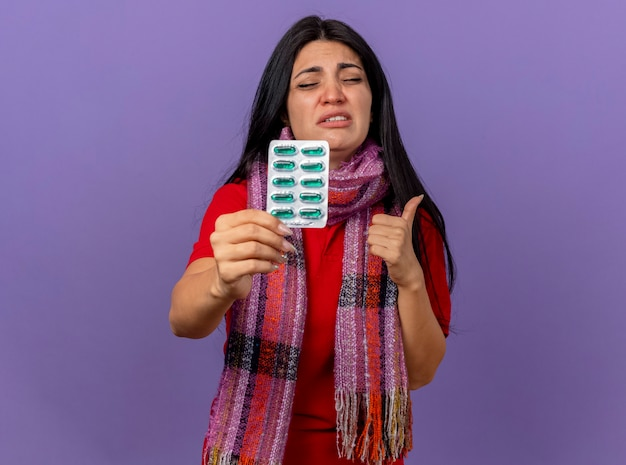 カプセルのパックを示すスカーフを身に着けている若い白人の病気の少女を痛め、コピースペースで紫色の壁に隔離された目を閉じて親指を立てる