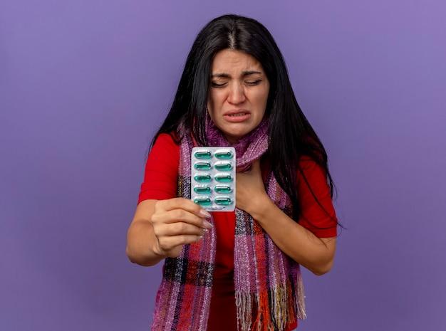 コピースペースで紫色の壁に隔離された目を閉じて胸に手を置くカプセルのパックを示すスカーフを身に着けている痛む若い白人の病気の女の子