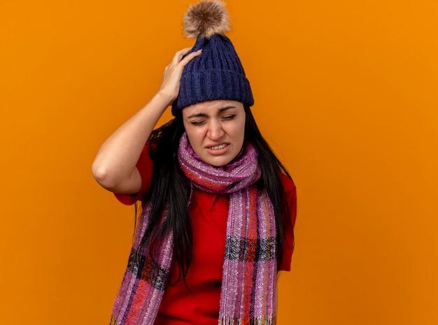冬の帽子とスカーフを身に着けている若い白人の病気の少女がコピースペースでオレンジ色の壁に隔離された目を閉じて頭に手を置いて痛む