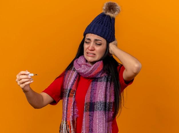 Giovane ragazza malata caucasica dolorante che indossa cappello invernale e sciarpa che tiene e che esamina termometro che mette la mano sulla testa isolata sulla parete arancio con lo spazio della copia