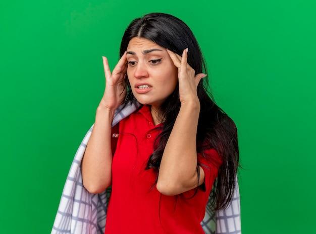 Giovane ragazza malata caucasica dolorante avvolta in un plaid che guarda giù tenendo le mani sulle tempie isolate su priorità bassa verde con lo spazio della copia