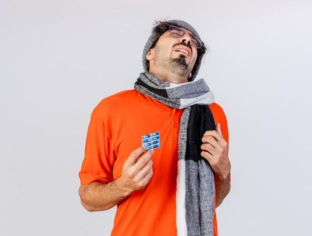 Aching young caucasian ill man wearing glasses winter hat and scarf holding pack of medical capsules touching chest isolated on white background with copy space