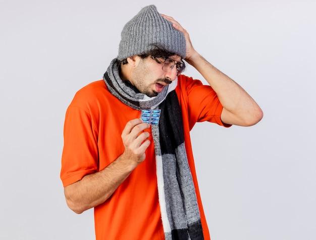 Giovane uomo malato caucasico dolorante che indossa occhiali inverno cappello e sciarpa che tiene il pacchetto di capsule mediche toccando la testa isolata sul muro bianco