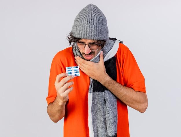 Giovane uomo malato caucasico dolorante che indossa occhiali inverno cappello e sciarpa che tiene il pacchetto di capsule mediche toccando la gola con gli occhi chiusi isolato sul muro bianco con lo spazio della copia