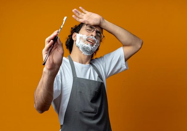 Giovane barbiere maschio caucasico dolorante con gli occhiali e fascia per capelli ondulati in uniforme che tiene il rasoio mettendo la mano sulla testa con crema da barba messa sul viso con gli occhi chiusi