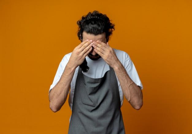 젊은 백인 남성 이발사 유니폼과 안경을 쓰고 머리 가위를 잡고 두통이 복사 공간이 오렌지 배경에 고립 된 데 이마에 손을 댔다.
