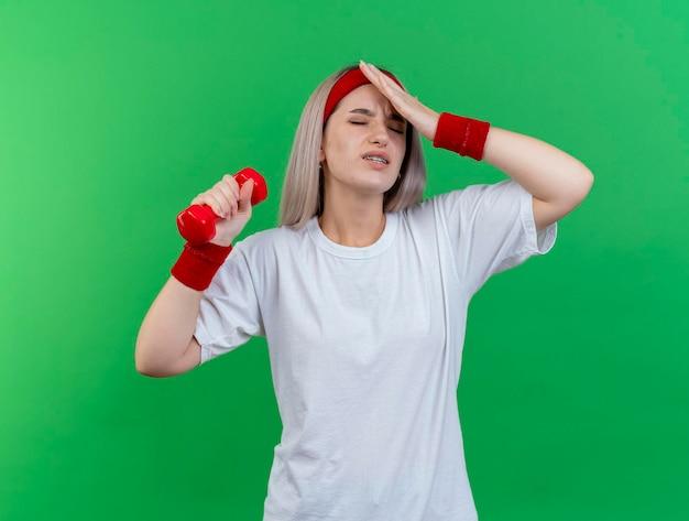 Giovane ragazza sportiva caucasica dolorante con le parentesi graffe che portano la fascia