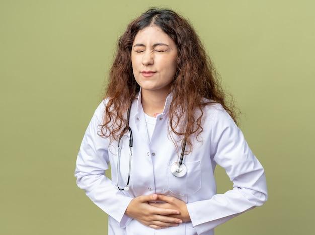 의료 가운을 입고 청진기를 입고 올리브 그린 벽에 눈을 감고 배꼽을 잡고 있는 아픈 젊은 여성 의사