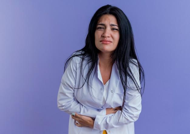 Giovane medico femminile dolorante che indossa veste medica alla ricerca della pancia della holding