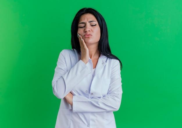 Болит молодая женщина-врач в медицинском халате, положив руку на щеку, страдающую от зубной боли, с закрытыми глазами, изолированными на зеленой стене с копией пространства