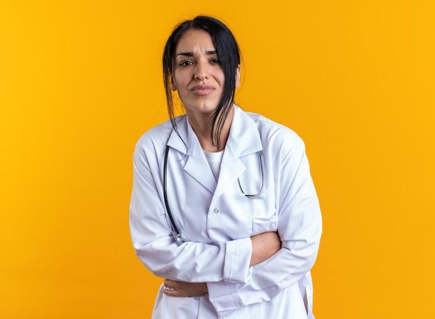 黄色の壁に隔離された聴診器で胃をつかんで医療ローブを着て痛む若い女性医師