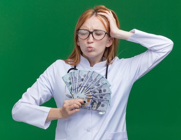 Giovane dottoressa dolorante allo zenzero che indossa abito medico e stetoscopio con occhiali che tengono soldi guardando in basso tenendo la mano sulla testa avendo mal di testa isolato sul muro verde
