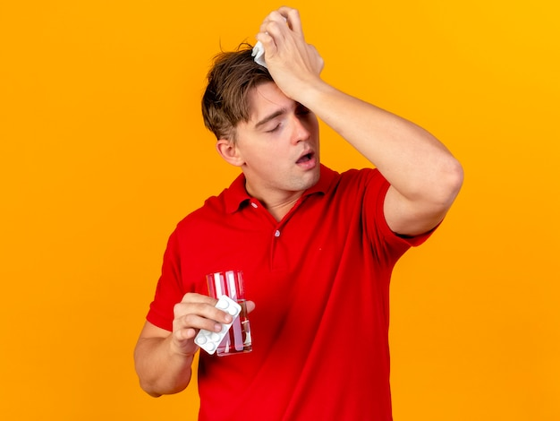 Aching young handsome blonde ill man holding pack of medical tablets glass of water and napkin touching head having headache with closed eyes isolated on orange wall