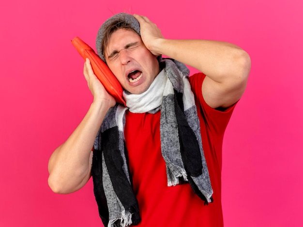 湯たんぽを持った冬の帽子とスカーフを身に着けている若いハンサムな金髪の病気の人がピンクの壁に隔離された目を閉じて頭に手を保ちながら顔に触れて痛む