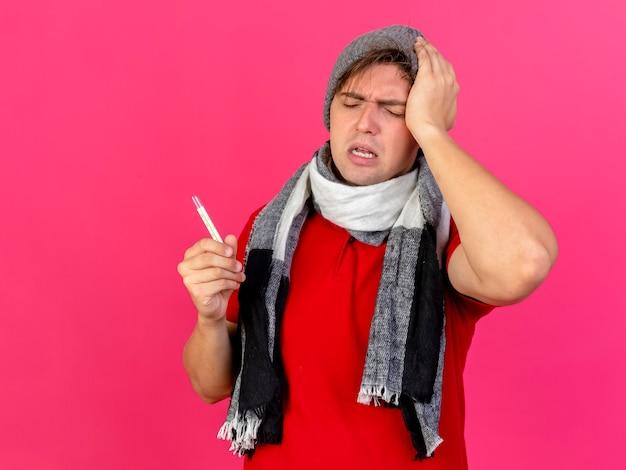 분홍색 벽에 고립 된 닫힌 눈으로 머리를 만지고 온도계를 들고 겨울 모자와 스카프를 착용하는 젊은 잘 생긴 금발 아픈 남자가 아프다