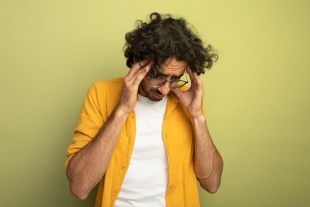 Giovane uomo caucasico bello dolorante con gli occhiali che mette le mani sulla testa guardando in basso che soffrono di mal di testa isolato sulla parete verde oliva con lo spazio della copia
