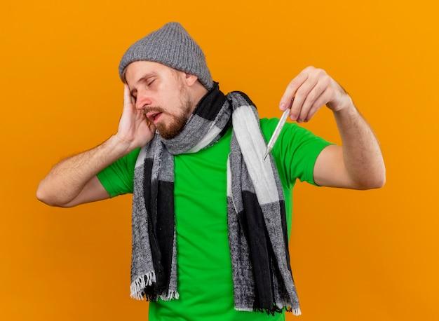 冬の帽子とスカーフを身に着けている若いハンサムな病気の人がオレンジ色の壁に隔離された目を閉じて頭に触れる温度計を保持している痛む