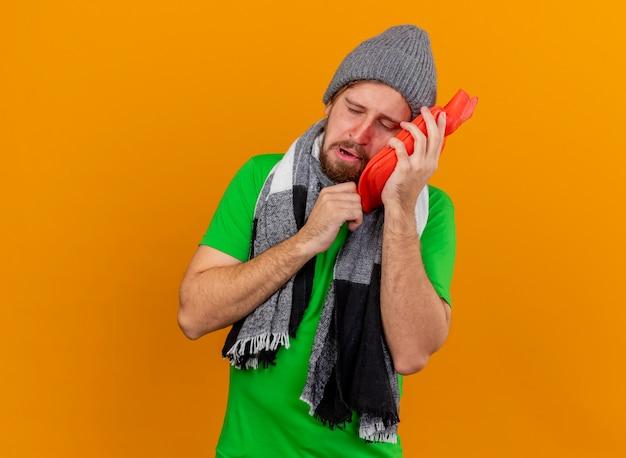 Giovane uomo malato bello dolorante che indossa cappello invernale e sciarpa che tiene la borsa dell'acqua calda che tocca il fronte con gli occhi chiusi isolati sulla parete arancione