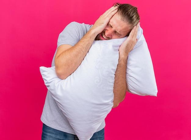 Больной молодой красивый славянский больной обнимает подушку, держит голову с закрытыми глазами, страдает от головной боли, изолированной на розовой стене