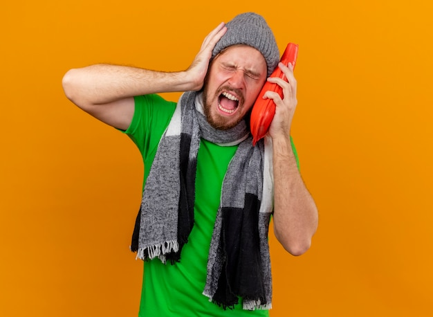 Giovane bello slavo malato dolorante che indossa cappello invernale e sciarpa che tiene la borsa dell'acqua calda che tocca il fronte con esso tenendo la mano sulla testa che ha mal di testa isolato sulla parete arancione con lo spazio della copia