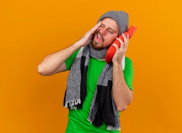 Giovane bello slavo malato dolorante che indossa cappello invernale e sciarpa che tiene la borsa dell'acqua calda che tocca il fronte con esso con gli occhi chiusi isolati sulla parete arancione con lo spazio della copia