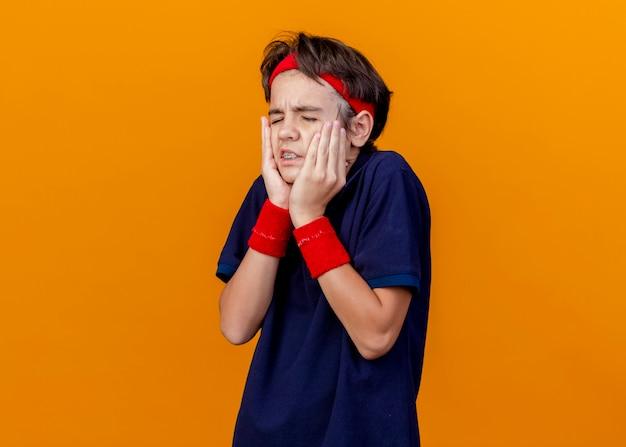 Больной молодой красивый спортивный мальчик с головной повязкой и браслетами с зубными скобами, держа руки на лице с закрытыми глазами, изолированными на оранжевой стене