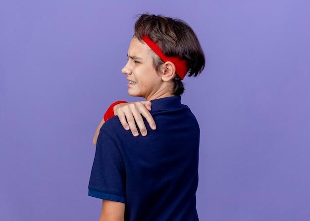 ヘッドバンドとリストバンドを身に着けている痛む若いハンサムなスポーティな少年は、コピースペースで紫色の壁に隔離された背中に手を保ちながら後ろのビューに立っている歯科用ブレースで立っています